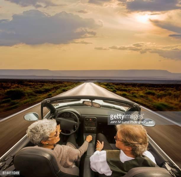 Older Hispanic couple driving on rural road in desert landscape