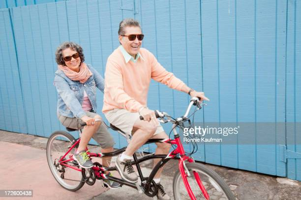 Older Hispanic couple riding tandem bicycle