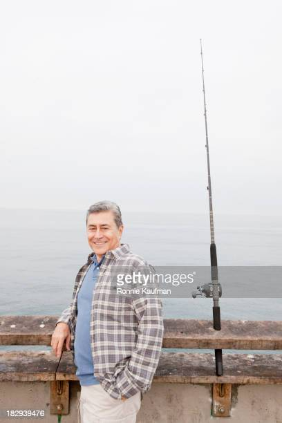 Older Hispanic man fishing on dock
