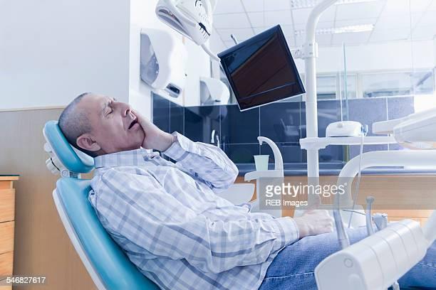 Older Hispanic man holding cheek in chair at dentist