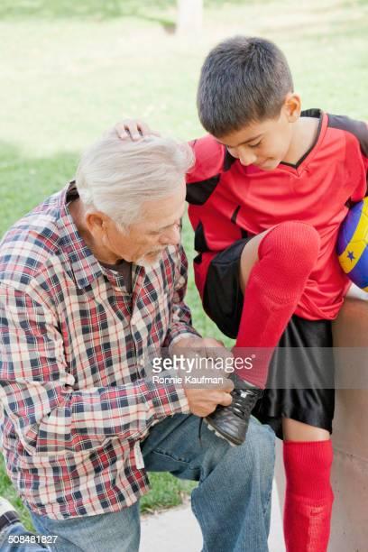 Older Hispanic man tying grandson's shoelaces