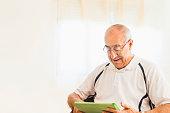 Older Hispanic man using digital tablet