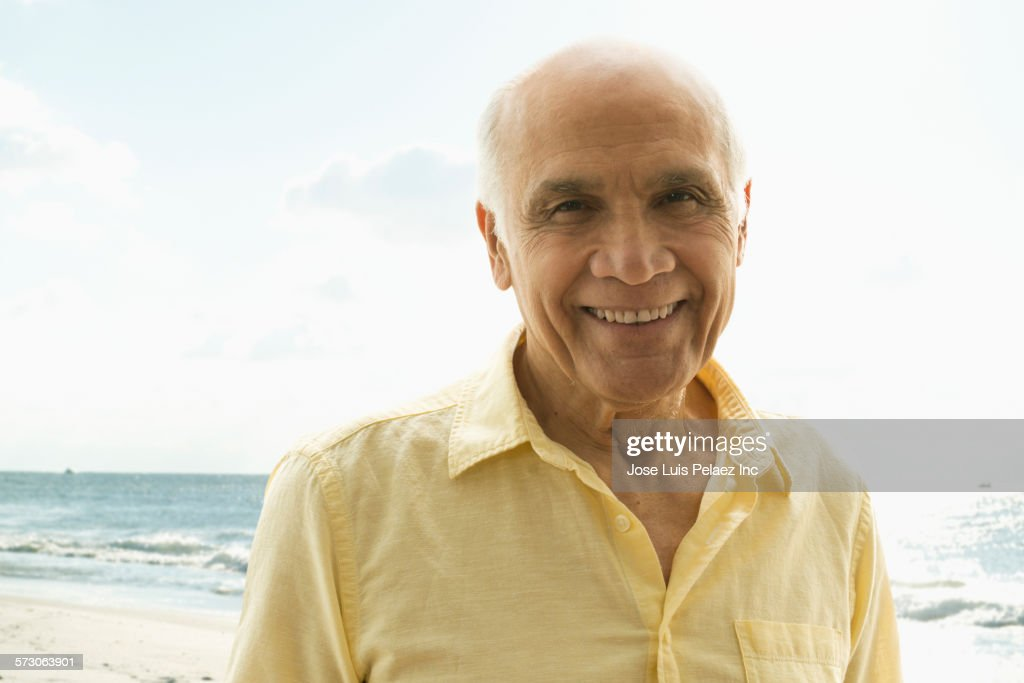 Older Hispanic man walking on beach