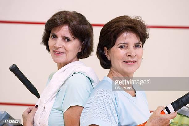 Older Hispanic twins playing squash