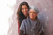 Older Hispanic woman and granddaughter smiling