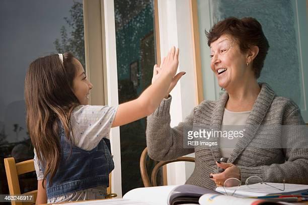 Older Hispanic woman high-fiving granddaughter