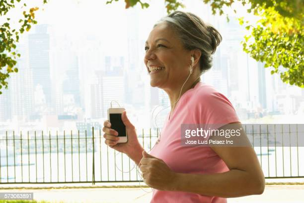Older Hispanic woman jogging in urban park, West New York, New Jersey, United States