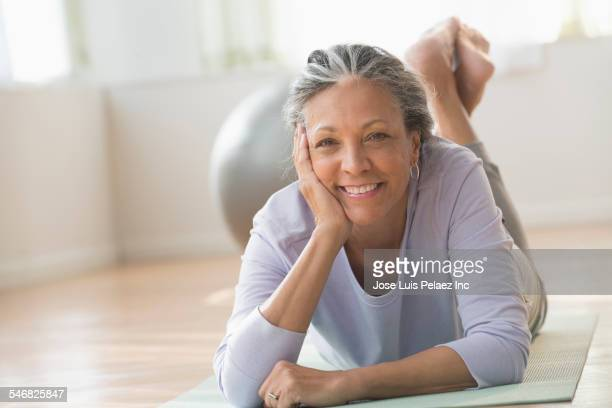 Older Hispanic woman laying on exercise mat