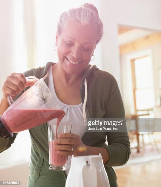 Older Hispanic woman making fruit smoothie