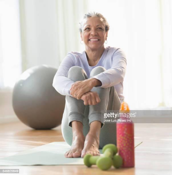 Older Hispanic woman sitting on exercise mat