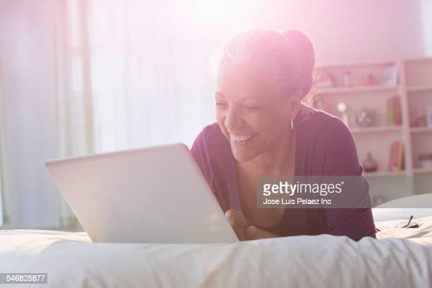 Older Hispanic woman using laptop on bed