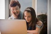 Older Hispanic woman using laptop with granddaughter