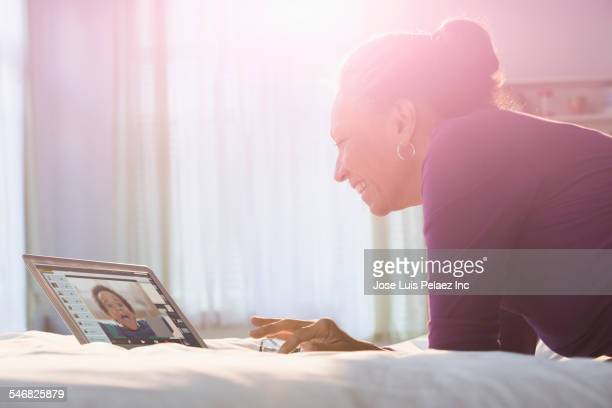 Older Hispanic woman video-chatting with grandson on laptop