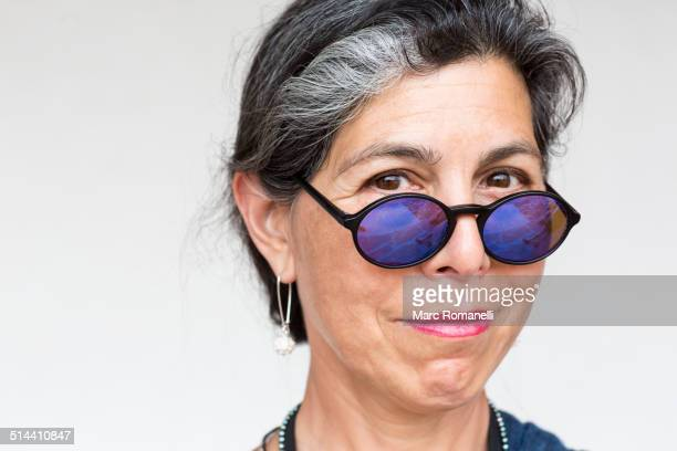 Older Hispanic woman wearing blue sunglasses