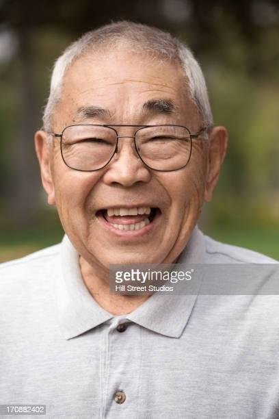 Older Japanese man smiling outdoors
