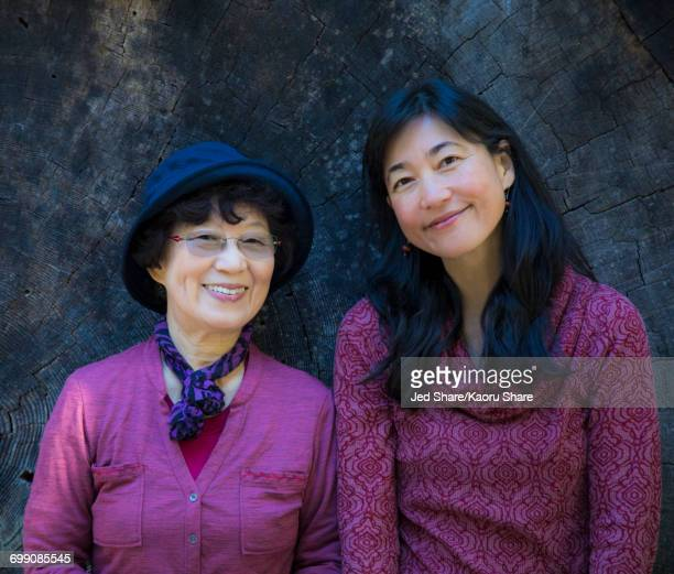 Older Japanese mother and daughter posing at tree slice