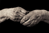 Black and white image of an older lady's hands clasped in grief wearing her late husbands wedding ring. Concept of loss, mourning and loneliness in old age..
