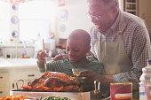 Older man and grandson cooking together in kitchen