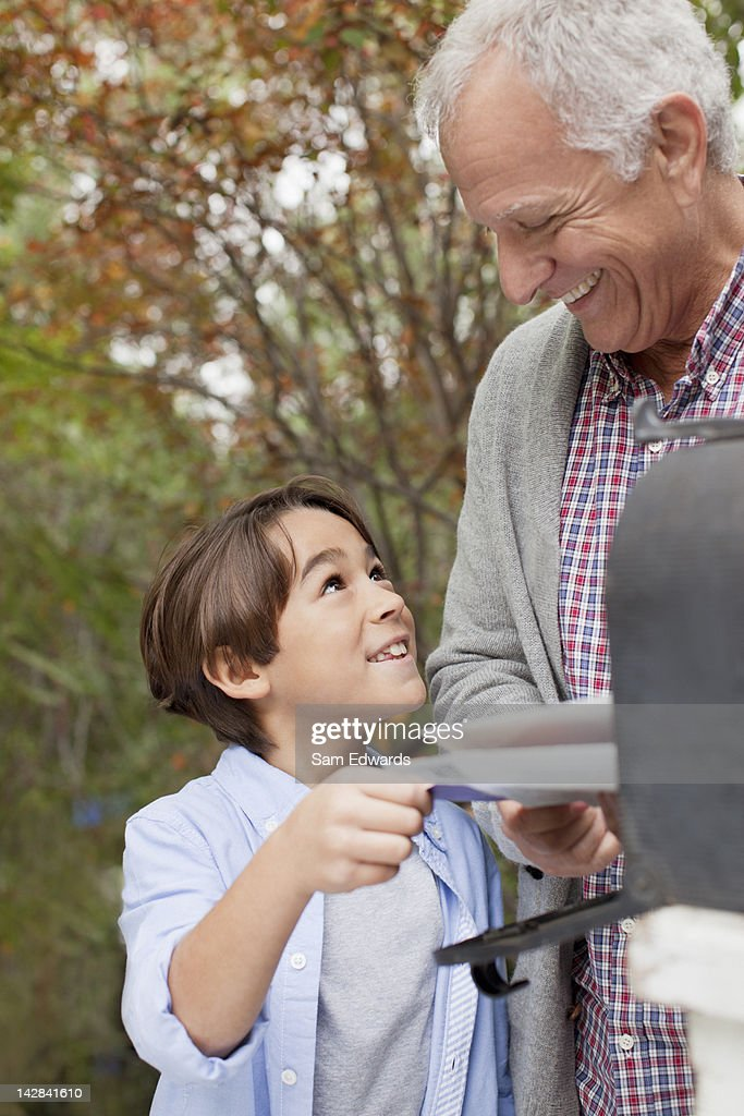 Older man and grandson opening mailbox : Stock Photo