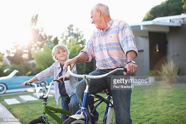 Hombre mayor envenenado y nieto montando una bicicleta al aire libre