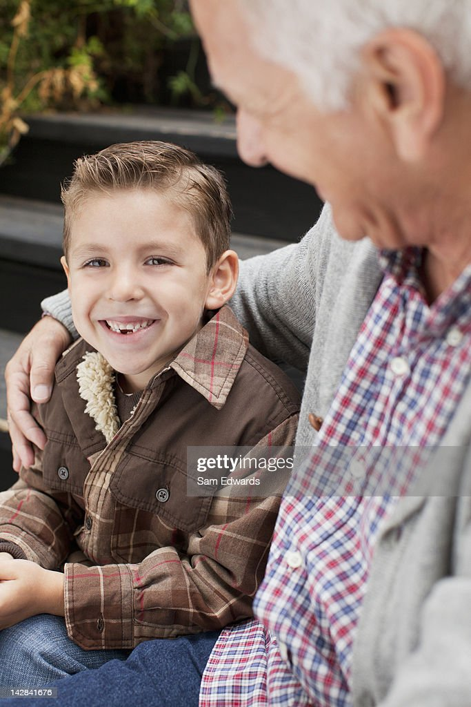 Older man and grandson sitting on steps : Stock Photo