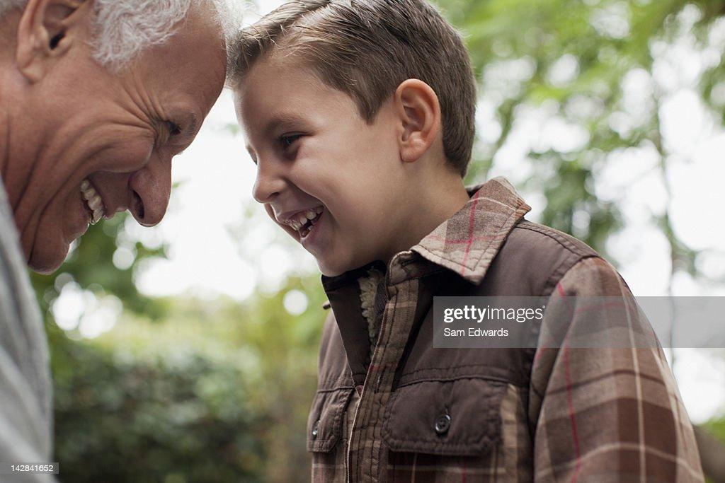 Older man and grandson smiling together