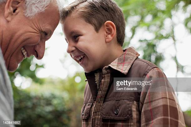 Older man and grandson smiling together