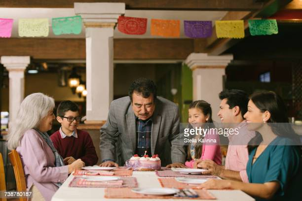 Older man blowing out candles on birthday cake in restaurant