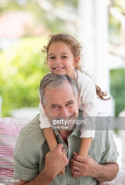Older man carrying granddaughter piggyback