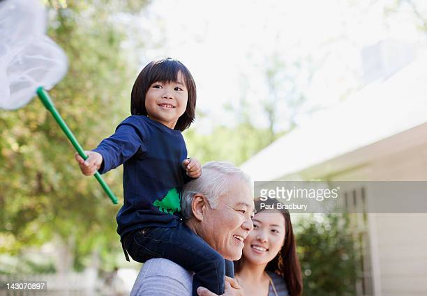Older man carrying grandson on shoulders