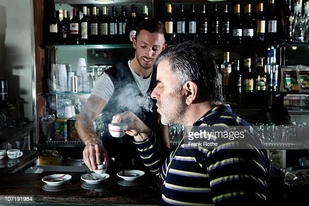 older man enjoys his coffee in a espresso bar