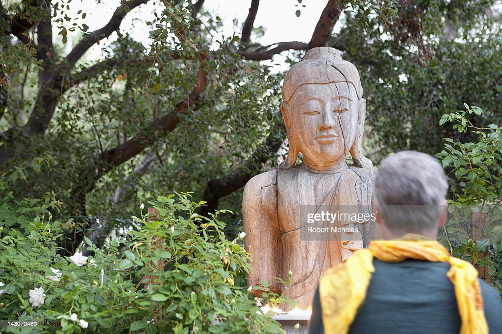 Older man examining Buddha statue : Stock Photo