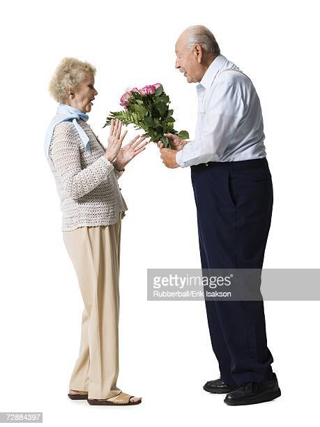 Older man giving wife bouquet of pink roses