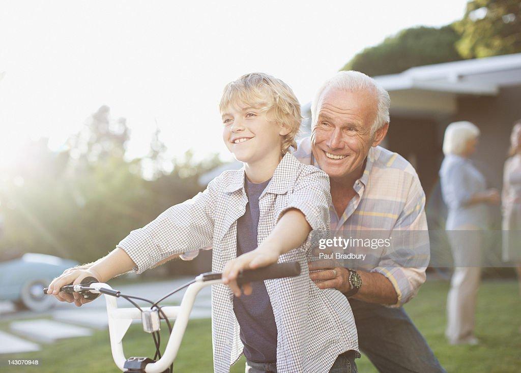 Older man helping grandson ride bicycle