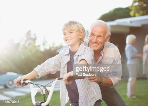 Older man helping grandson ride bicycle