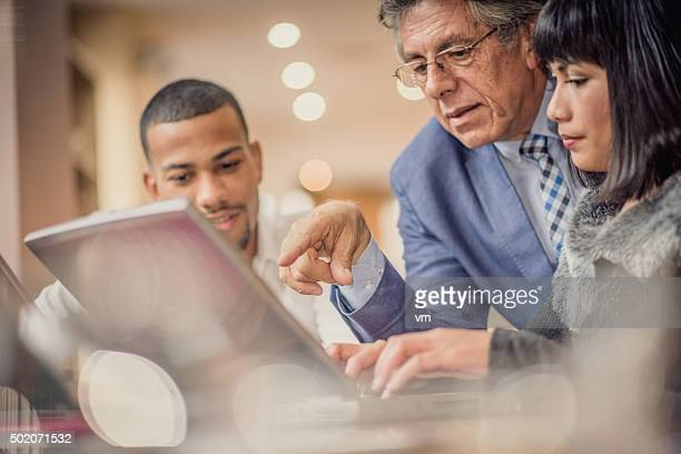 Older man helping his younger colleagues in a relaxed environment