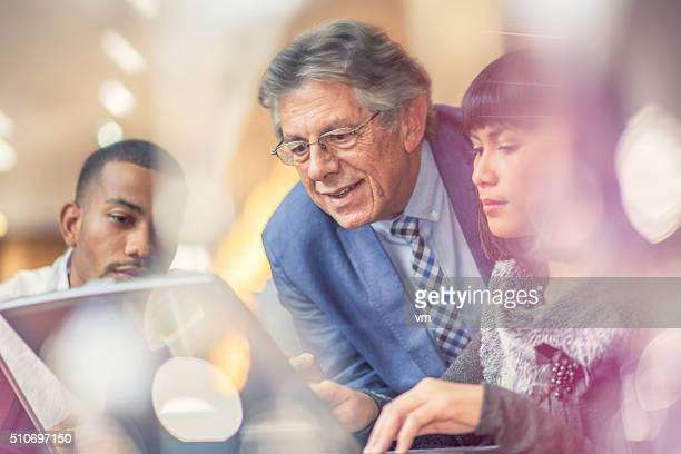 Älterer Mann hilft seinem jüngeren Kollegen in einem entspannten Ambiente
