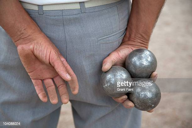 Older man holding balls boules for game.