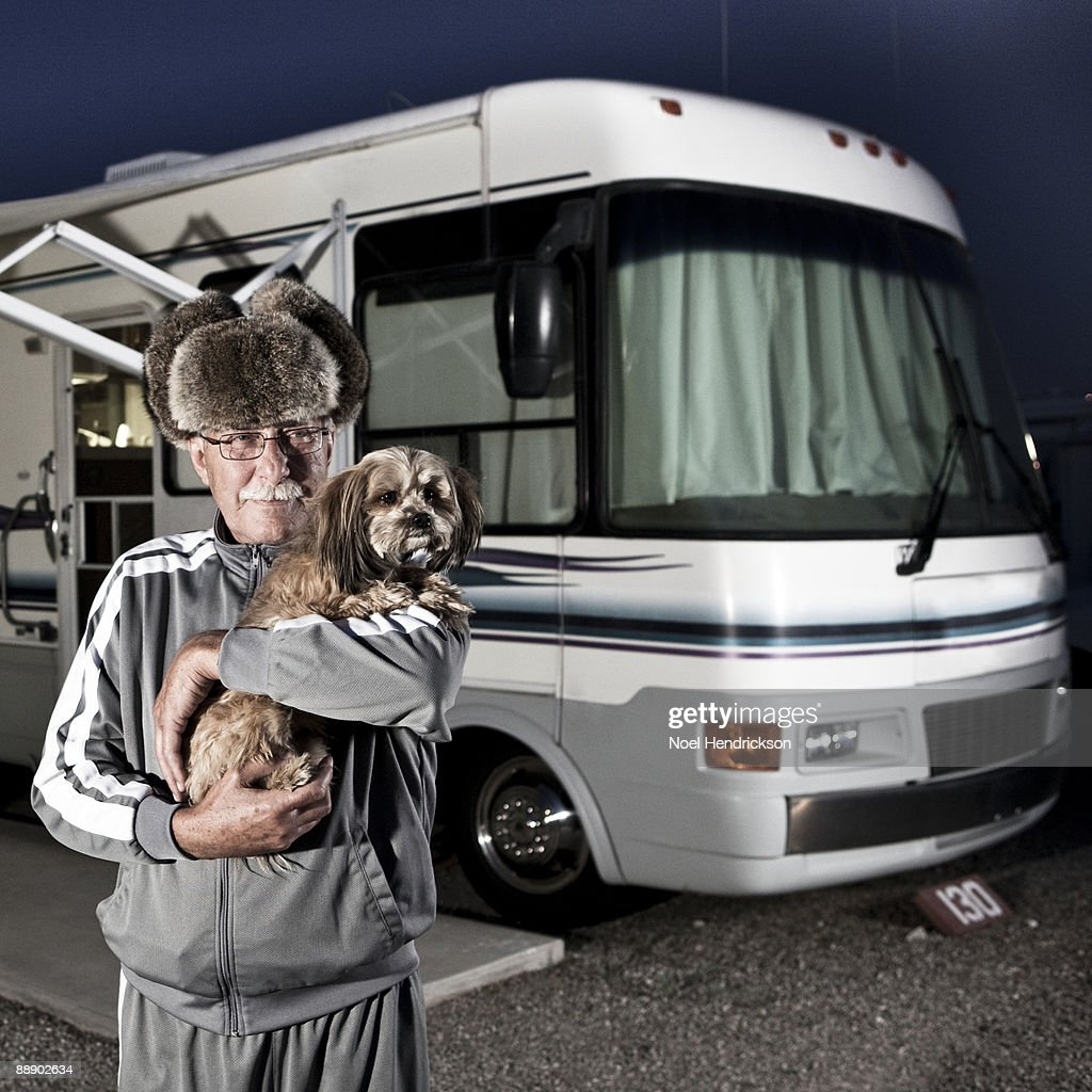 Older man holding dog in front of RV : Stock Photo