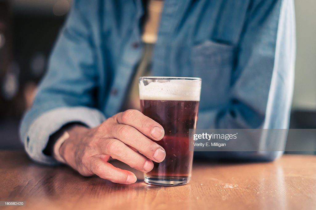Older man holding glass for beer