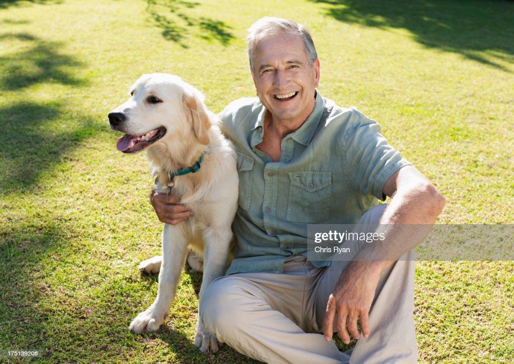 Older man hugging dog in backyard : Stock Photo