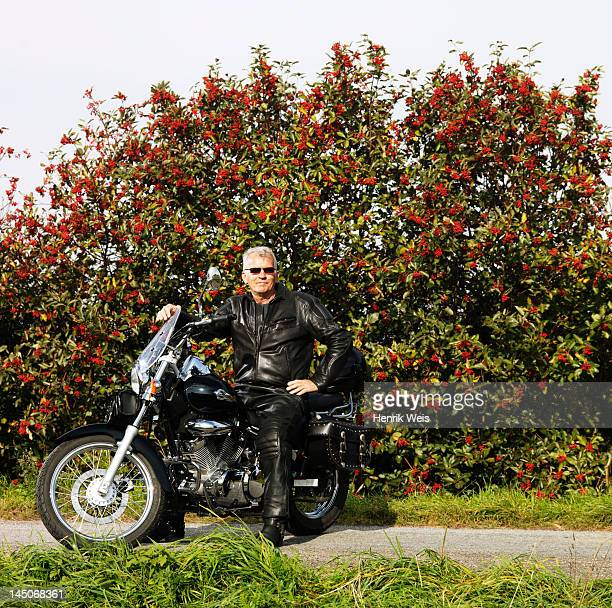 Older man in leather on motorcycle