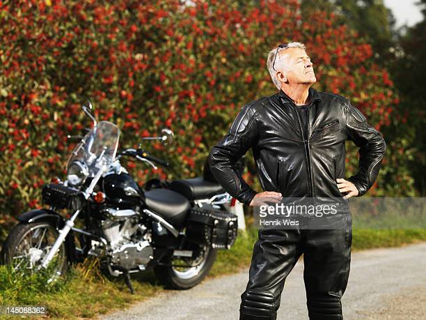 Older man in leather with motorcycle