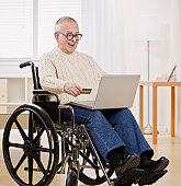 Older disabled man in wheelchair using credit card to conveniently shop on the internet.