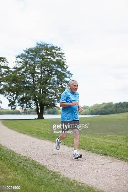 Older man jogging on dirt path