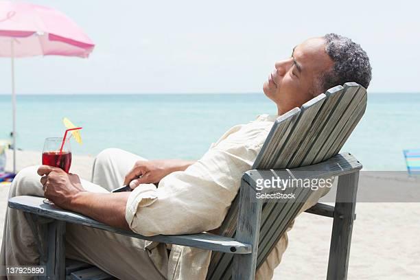 Homme détente sur la plage d'un fauteuil avec une boisson