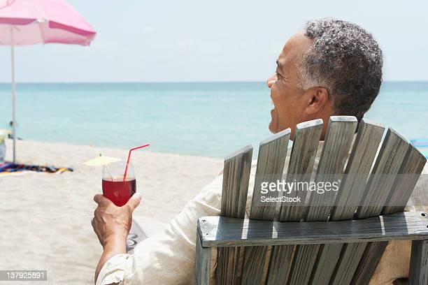 Ältere Mann Entspannen am Strand mit Getränk Stuhl