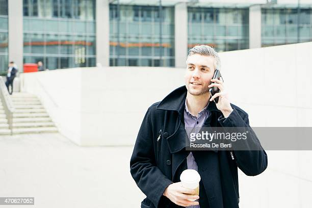 Older man on cell phone outside of building with coffee