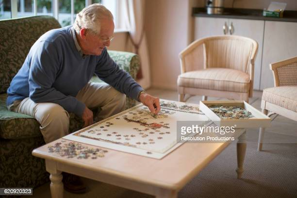Older man on sofa solving jigsaw puzzle