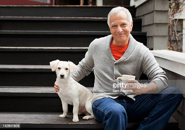 Older man petting puppy on steps outdoors